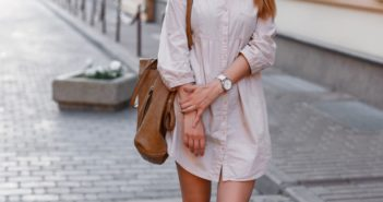 Young beautiful woman in sunglasses dress and sneakers walking in the city